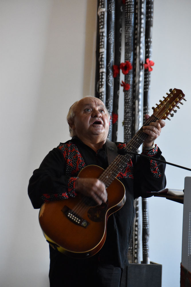 Uncle Johnny Huckle sings a song during the service